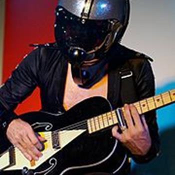 Man in crash helmet playing an electric guitar